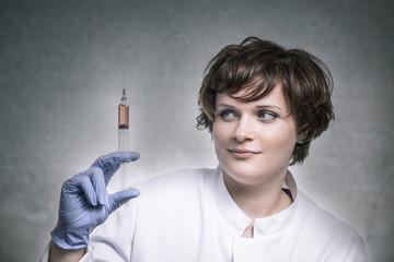 Wissenschaftlerin beäugt Spritze mit roter Flüssigkeit