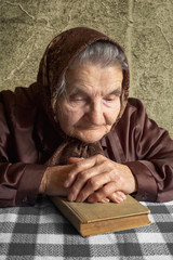 Elderly woman holds bible and pray.