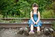 little girl sitting on railway