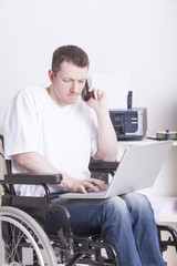 young man in wheelchair using a laptop