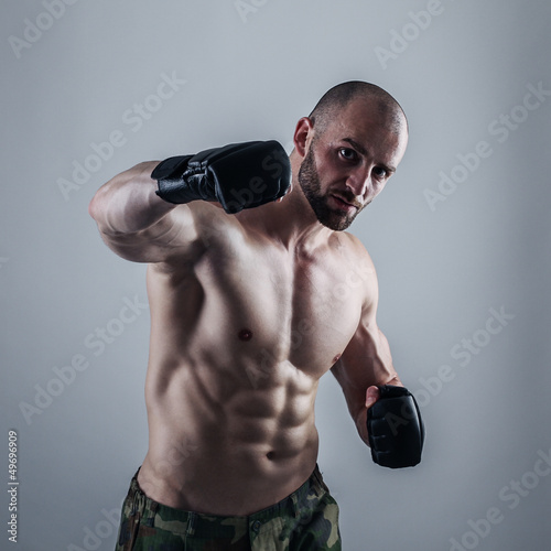 Muscular man with the gloves striking a punch