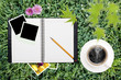 notebook with coffee and Polaroid frame on grass background