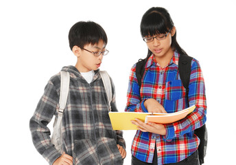 school boy and girl with backpacks holding books smiling