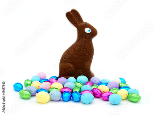 Chocolate Easter bunny with pile of colorful eggs