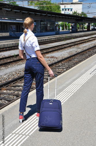 Girl with a suitcase at the train station