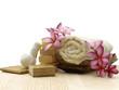 Spa setting with frangipani, soap, towel, candle on board