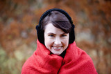 A woman wrapped up in a blanket wearing earmuffs