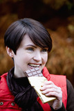A woman eating a bar of chocolate