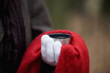 A woman holding a hot drink in autumn time, close up