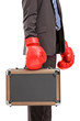 Businessman holding a briefcase with red boxer gloves