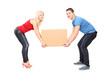 Full length portrait of a young couple trying to lift a box