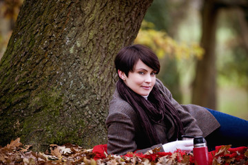 A woman sitting under a tree holding a hot drink in autumn