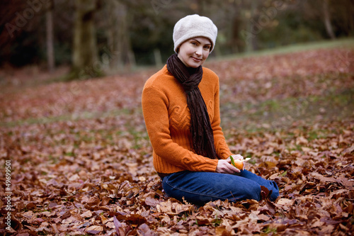 A woman sitting on the ground peeling a clementine