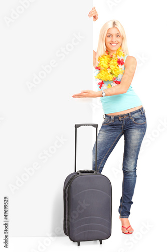 Full length portrait of a young female with suitcase pointing on