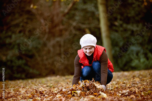 A woman gathering autumn leaves