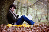 A woman sitting under a tree in autumn time, holding a book