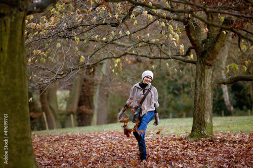 A woman kicking leaves in autumn time