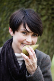 A woman eating a pear in autumn time