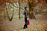 A woman walking in autumn time holding a blanket and flask