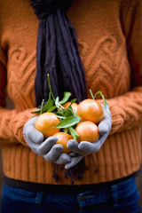 A woman holding a handful of clementines