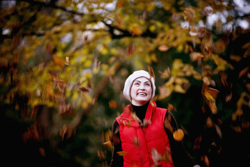 A woman standing amongst falling autumn leaves