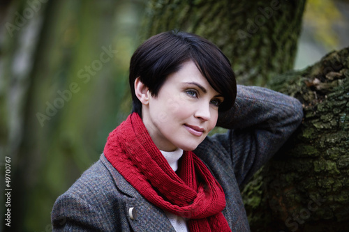 A woman leaning against a tree in autumn time