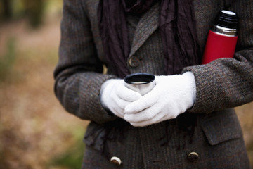 A woman holding a hot drink and flask outside in autumn