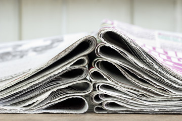 closeup pile of newspaper on wooden background