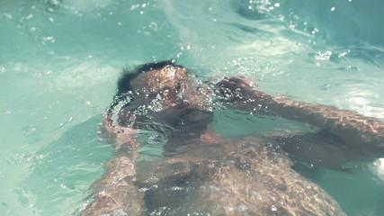 Man relaxing in swimming pool, slow motion shot at 120fps