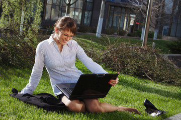 Woman lying on grass with laptop with business building on back
