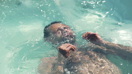 Man relaxing in swimming pool, slow motion shot at 240fps