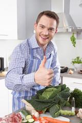 Der glückliche lachende Hausmann in der Küche