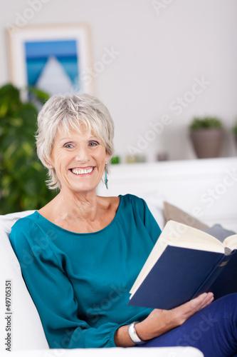 lächelnde seniorin liest ein buch