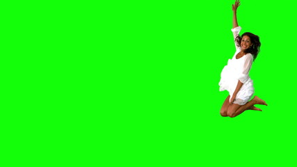 Girl in white jumping on green screen with large copy space