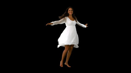 Girl in white dress twirling on black background