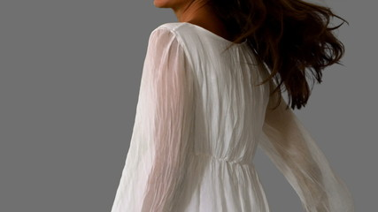 Girl in white dress twirling on grey background close up