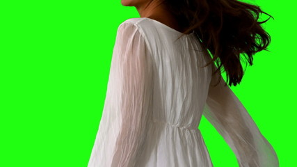 Girl in white dress twirling on green screen close up