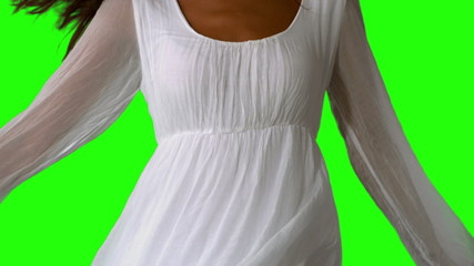 Girl in white dress turning on green screen close up