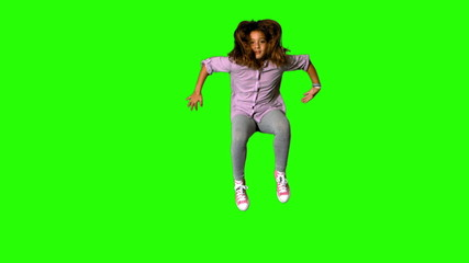 Happy little girl jumping on green screen