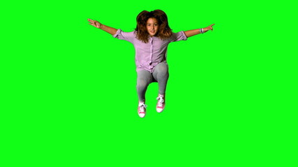 Happy little girl jumping up and down on green screen