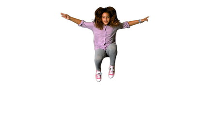 Happy little girl jumping up and down on white background