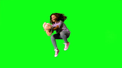 Happy little girl jumping up and catching teddy on green screen