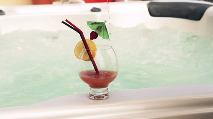 Pouring a drink into a glass over the jacuzzi, slow motion shot