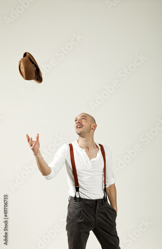 man throws his hat in air
