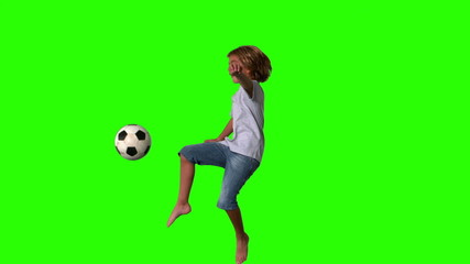 Boy jumping and kicking football on green screen