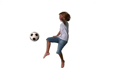 Boy jumping and kicking football on white background