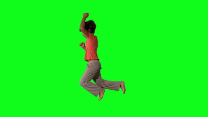 Side view of boy jumping on green screen