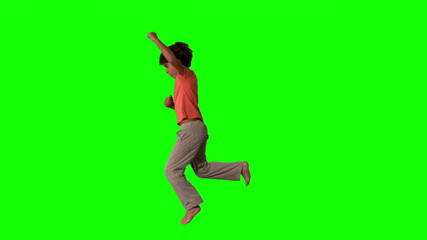 Side view of boy jumping up on green screen