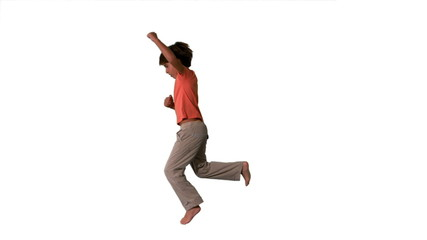 Side view of boy jumping up on white background