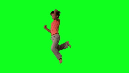 Side view of boy jumping up and down on green screen